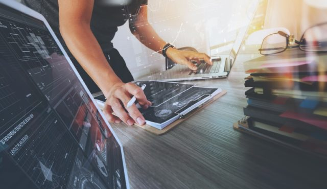 Woman browsing on a laptop with a tablet on the side